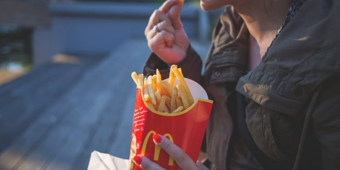 woman eating french fries and holding a container of french fries
