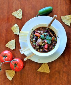 image of black bean soup with chips tomatoes and jalapeno