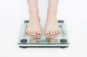 image of feet stepping on a scale to weigh