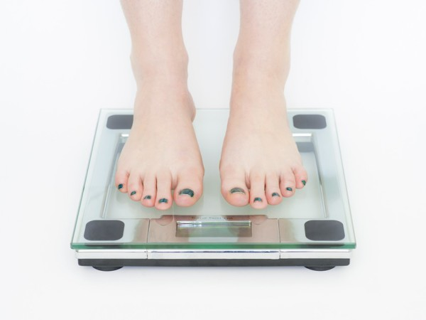 best weight loss tip ever image of feet stepping on a scale to weigh