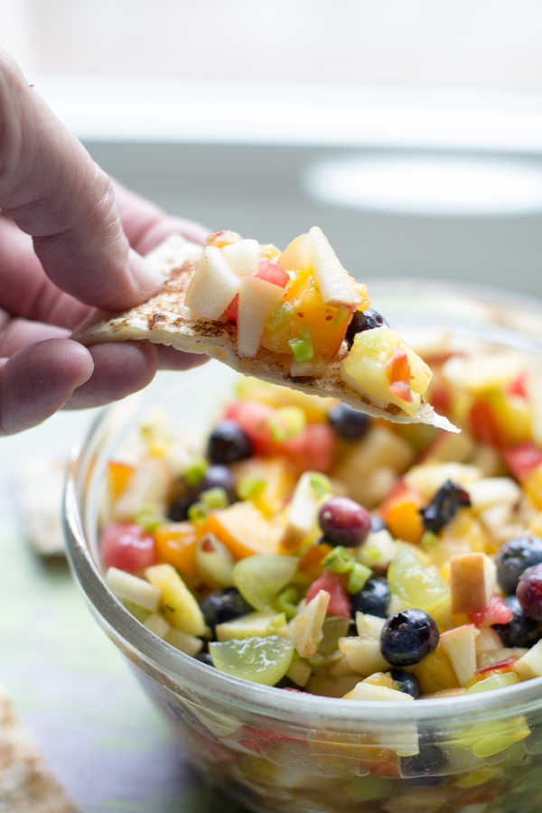 image of a bowl of creamy fruit salsa by intentionally eat with cindy newland with a and holding a cinnamon crisp chip full of creamy fruit salsa for healthy plant-based summer desserts