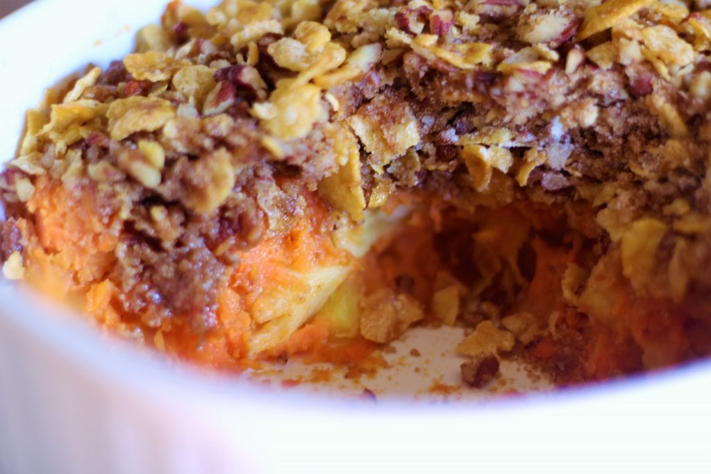 the best ever sweet potato casserole in a white casserole dish. Sweet potatoes with pineapple chunks covered with a nutty crumb topping.