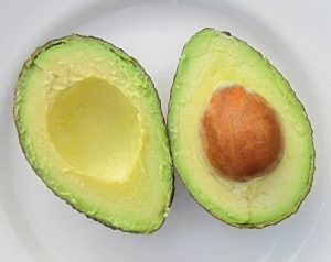 avocado cut in half one half with the pit