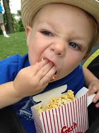 cheat day diet - little boy shoving popcorn in his mouth while holding a container of popcorn