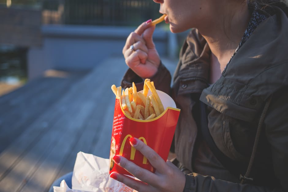 cheat day diet -woman eating french fries and holding a container of french fries