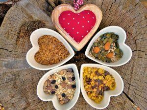 five heart shaped bowls filled with different superfoods trail mix ingredients