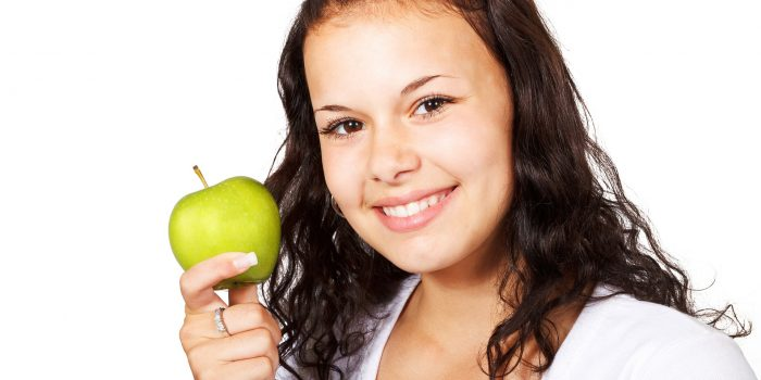 woman holding a granny smith apple