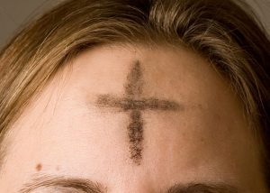 image of a blonde person with ashes in the mark of a cross on their forehead