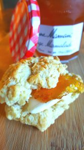 image of drop biscuit with marmalade and vegan butter spread on it.. A jar of marmalade in the background.