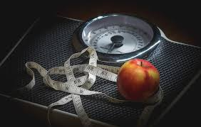 image of a scale with an apple and a tape measure on it