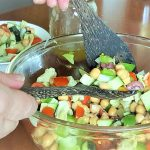 image of tangy greek chickpea salad in a glass bowl being tossed by a pair of wooden spoons.