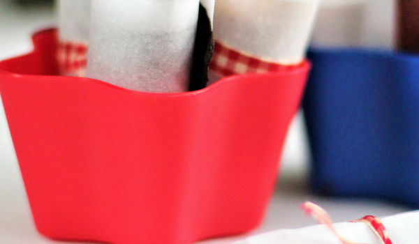 image of red and blue start shaped containers holding fruit roll-ups and one fruit roll -up on the table in front of the containers.
