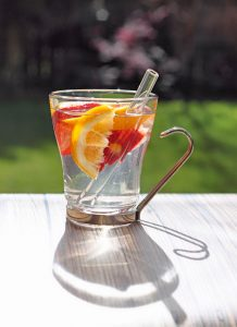 image of glass of water with grapefruit and orange slices and a glass straw