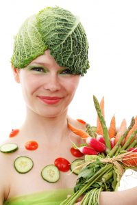 image of woman holding vegetables and wearing cabbage leaves on her head for 8 rules for clean eating