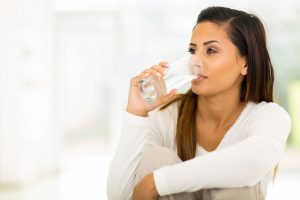 dark haired woman dressed in white drinking a glass of water for 10 tricks for healthy eating out by intentionally eat