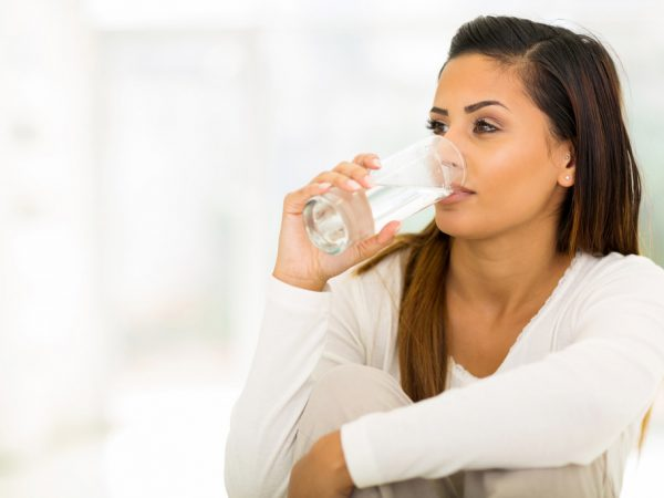 dark haired woman dressed in white drinking a glass of water
