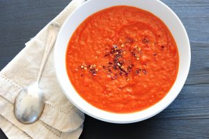 image of a white bowl filled with tomato soup and topped with black pepper. The bowl is placed on top of a white napkin with a spoon on it for 10 tricks for health eating out by intentionally eat