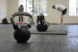 image of kettlebells on a gym floor with people in the background for how to start working out by intentionally eat