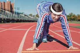image of a woman in a track suit and sweat band in a runners start position at the track for how to start working out by intentionally eat