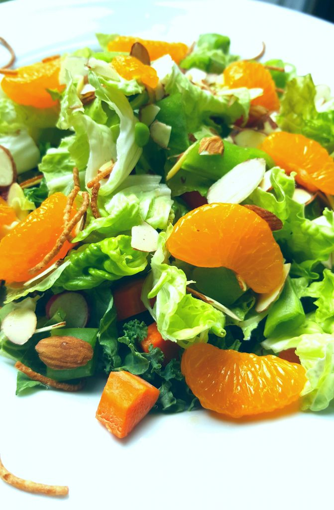 image of easy mandarin salad filled with mandarin oranges, snow peas, greens, almonds, and crispy noodles by intentionally eat