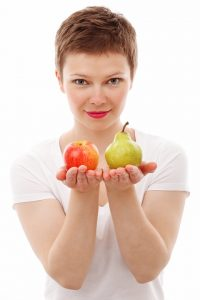 image of woman holding a pear in one hand and an apple in the other. freedom from overeating by intentionally eat