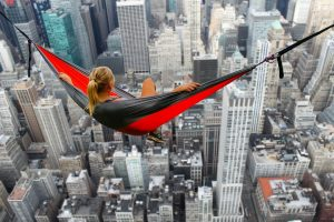 image of woman in a hammock swinging high over skyscrapers for living without fear by intentionally eat