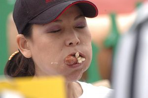 image of woman wearing a ballcap with eyes closed and mouth full of food. A hotdog and bun are sticking out of her mouth. freedom from overeating by intentionally eat