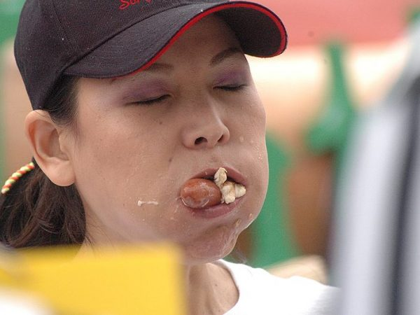 image of woman wearing a ballcap with eyes closed and mouth full of food. A hotdog and bun are sticking out of her mouth.