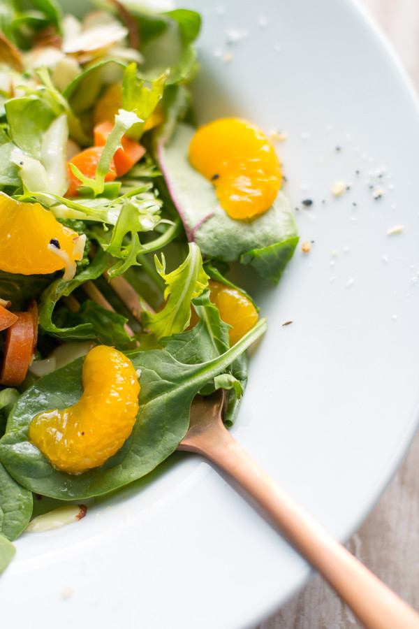 image of Easy Mandarin Salad Recipe in a white bowl with a bronze spoon