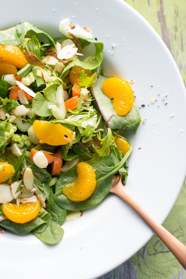 Easy Mandarin Salad Recipe by Intentionally Eat with Cindy Newland in a white bowl with a bronze fork