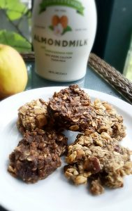 image of plate of irresistible apple pie protein cookies by intentionally eat with almond milk and an apple in the background
