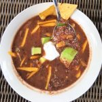 image of black bean soup -quick and easy by intentionally eat. The soup is in a white bowl topped with vegan cheese and sour cream, avocado and a tortilla chip.