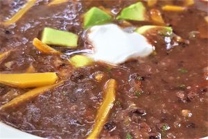 close up image of black bean soup- quick and easy by intentionally eat. Soup is topped with vegan cheese, sour cream and avocado slices.