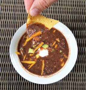 image of a white bowl filled with black bean soup - quick and easy by intentionally eat. A hand holding a tortilla chip with soup on it. Vegan cheese, sour cream and avocados top the soup.