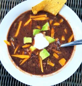 black bean soup -quick and easy by intentionally eat served in a white bowl and topped with vegan cheese, sour cream and avocado