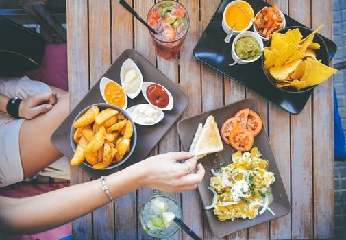 image of plates of food with hands reaching for it for 10 Tricks for Healthy Eating Out by Intentionally Eat