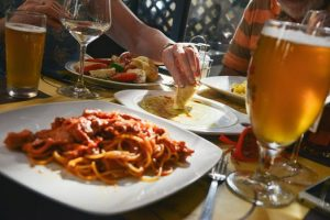 image of a table full of plates of food with glasses of beer and wine. A hand is reaching to dip a chip for 10 tricks to healthy eating out by intentionally eat