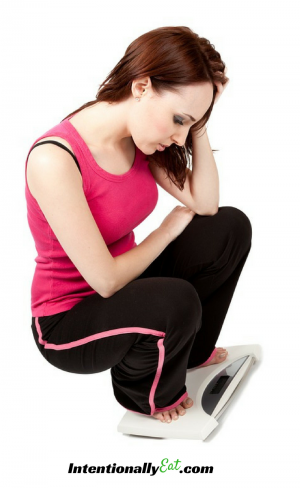 image of woman squatting on scale holding her head in her hand with frustration for healthy living devotional by intentionally eat