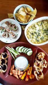 image of game day snacks such as tortilla roll-ups, veggies and dip, tortilla chips and healthy spinach artichoke dip by intentionally eat