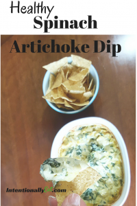 image of healthy spinach artichoke dip by intentionally eat with a hand dipping a tortilla chip
