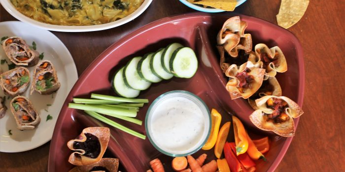 image of a variety of appetizers including Crunchy Taco Cups that are healthy by intentionally eat, vegetables and dip, and tortilla chips.