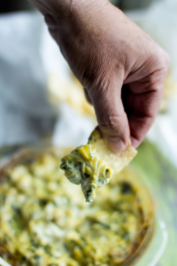 image of healthy spinach artichoke dip by intentionally eat with cindy newland with a hand holding a tortilla chip