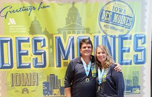 image of Cindy Newland with a half marathon medal around her neck and posing in front of the des moines iowa sign for how to have a healthy mindset by intentionally eat
