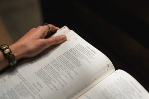 image of a hand on a Bible. The hand is wearing a bracelet and a ring.  Image for healthy living devotional is stinking thinking sabotaging your health by intentionally eat