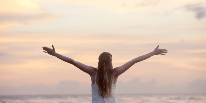 image of woman with her back to the camera, looking at the ocean with arms open wide for how to have a healthy attitude by intentionally eat