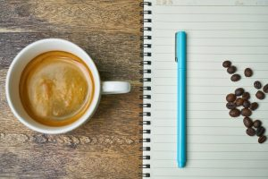 image of pumpkin spice creamer dairy free by intentionally eat in a cup of coffee next to a notebook and a teal pen