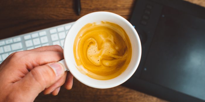 image of hand holding a cup of coffee with pumpkin spice creamer dairy free by intentionally eat