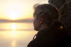 image of woman looking out toward a sunset for healthy living devotional is stinking thinking sabotaging your health by intentionally eat