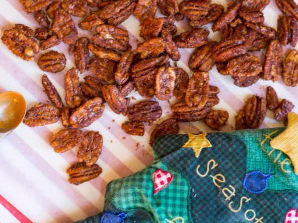 image of cinnamon candied nuts by intentionally eat with a christmas tree potholder next to the pecans