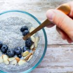 image of easy chia seed pudding by intentionally eat with blueberries, slivered almonds and a hand holding a spoon